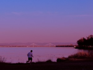 Man running with a bridge in the background